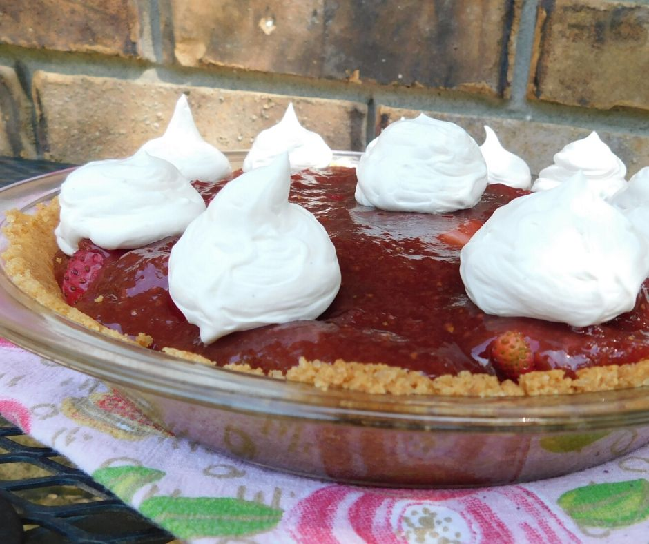 strawberry pie with whipped cream dollops on top of a flowered towel sitting outside on a table