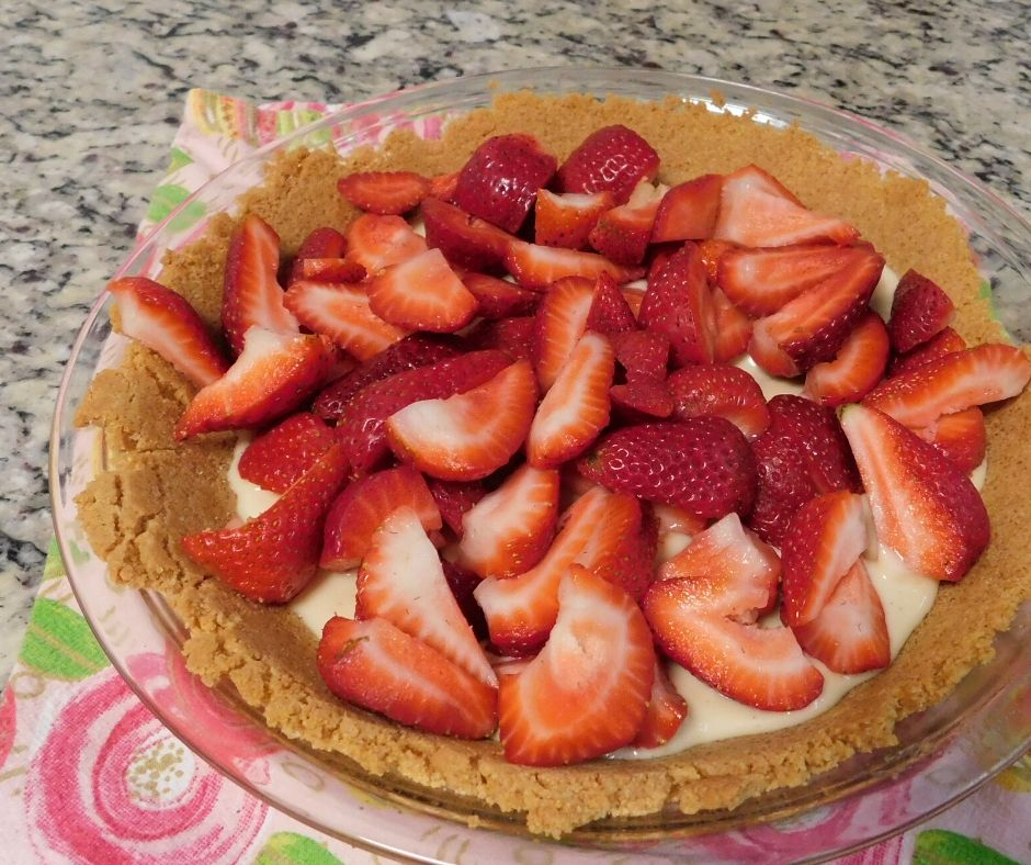 strawberries on top of cream cheese filling in a graham cracker crust