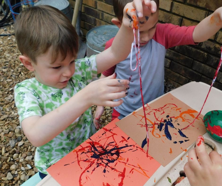 kids painting with yarn on paper in the backyard