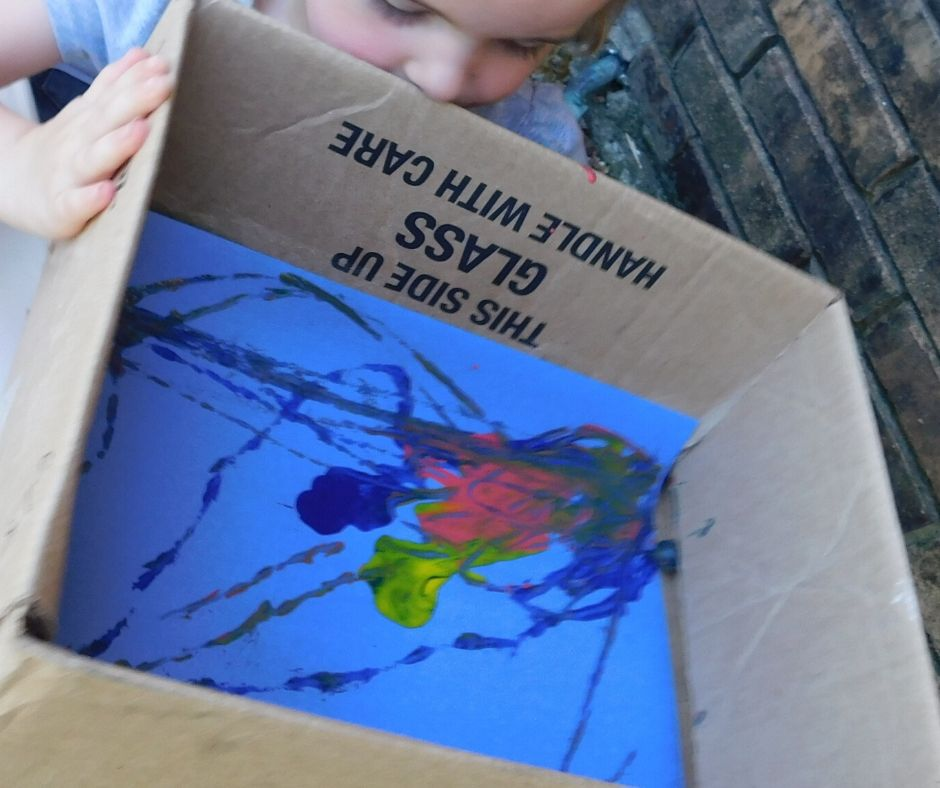child painting with a marble in a box