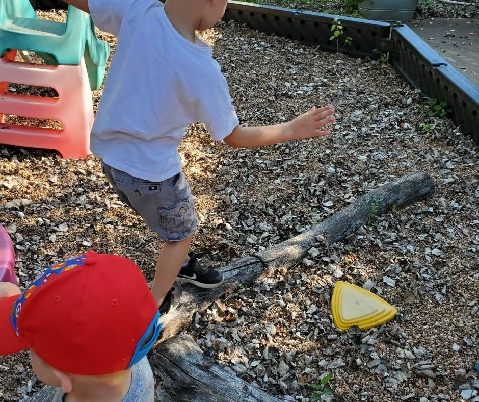 Kids playing on home daycare playground, walking along logs for balance