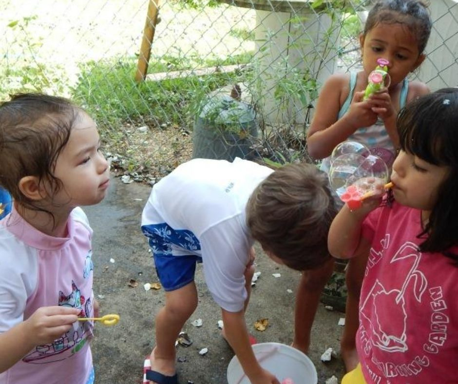 kids playing in water and bubbles on the back porch in home daycare
