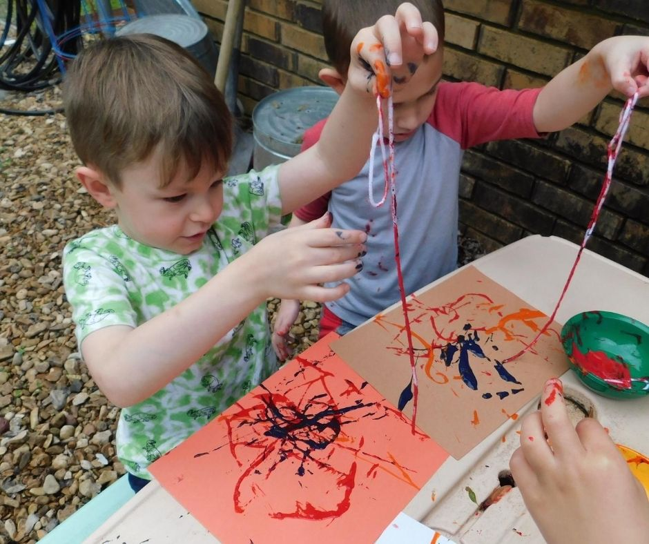 kids painting with yarn in home daycare