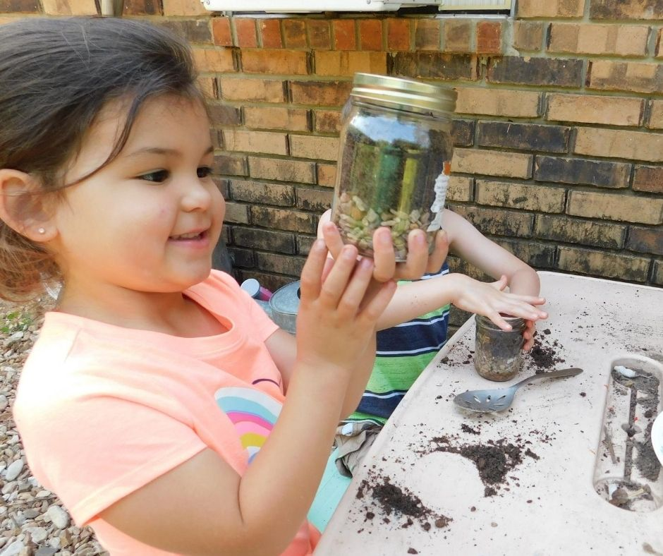 child building a terarrium in a jar, looking at her work