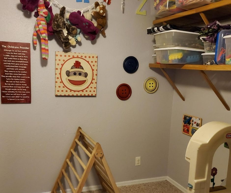 home daycare layout in playroom with pickler triangle, toy kitchen, stuffed animals on a chain and shelves full of toy sets