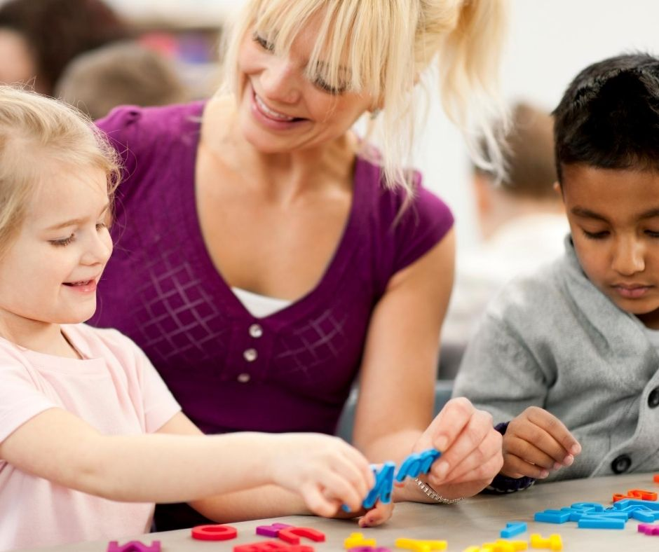 home daycare provider sitting at table teaching kids