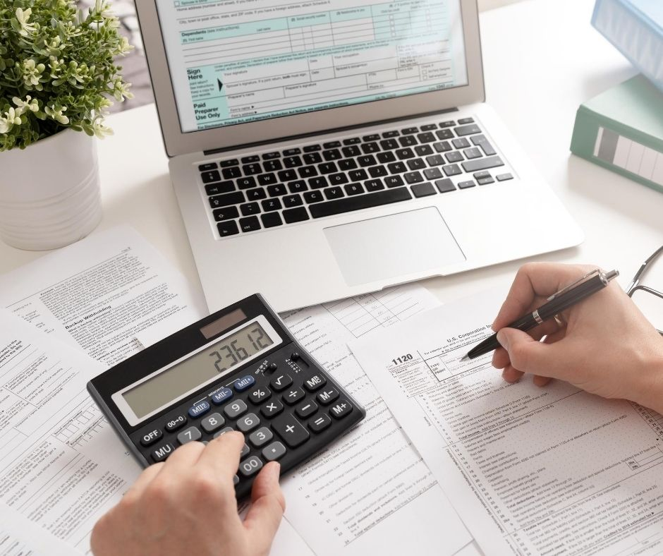 person figuring taxes with calculator and laptop as well as tax forms.