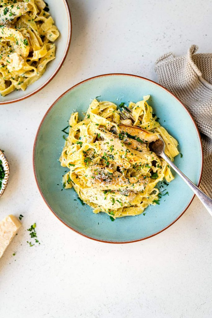 Chicken alfredo spun on a pretty blue plate with a fork. Great comfort food plate.