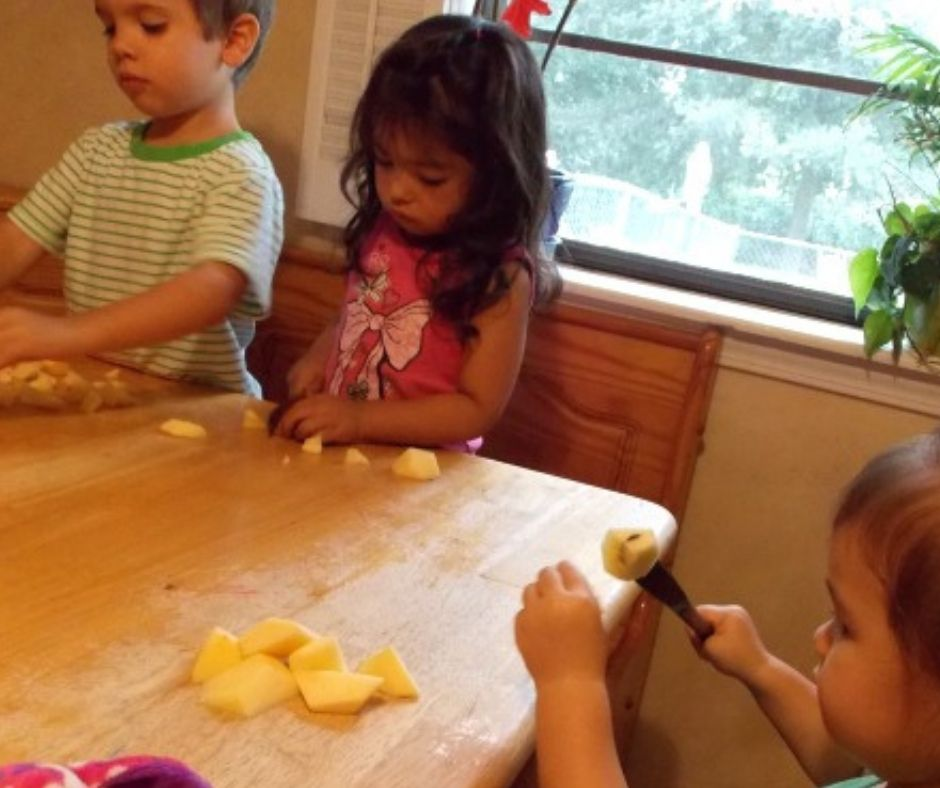 kids cutting up apples for applesauce in home daycare