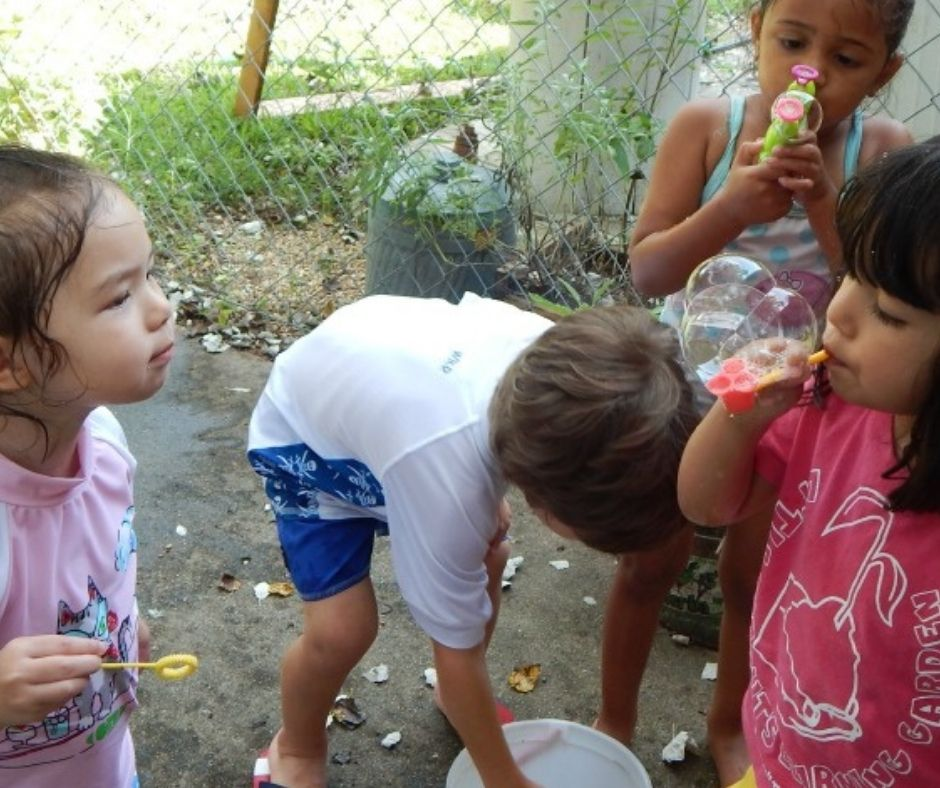 kids blowing bubbles at home daycare water party