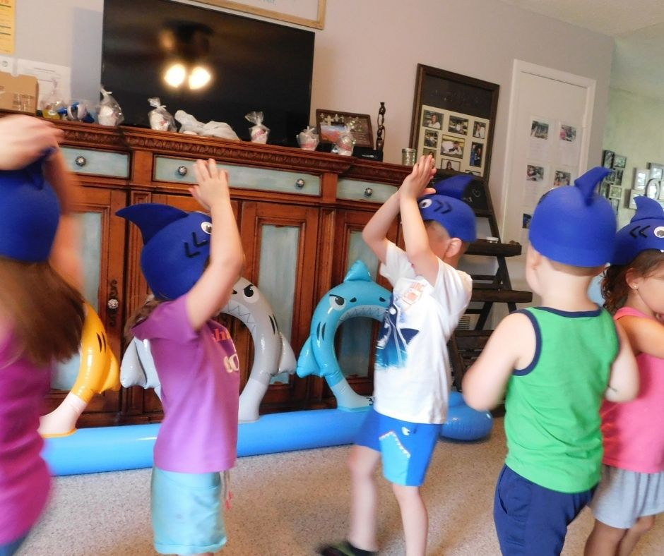 Kids singing baby shark and dancing wearing shark hats in home daycare