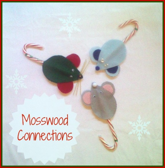 three felt mouse ornaments on a board with snowflakes.