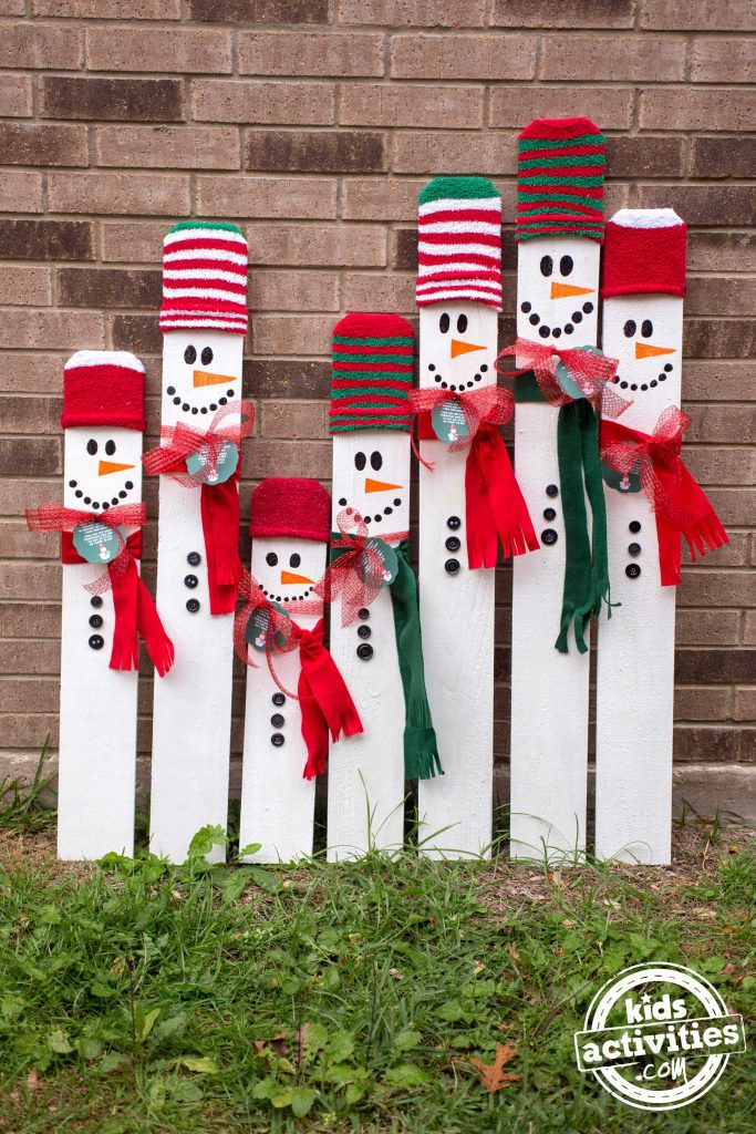 Leaning snowmen made from fence posts and decorated with hats and scarves