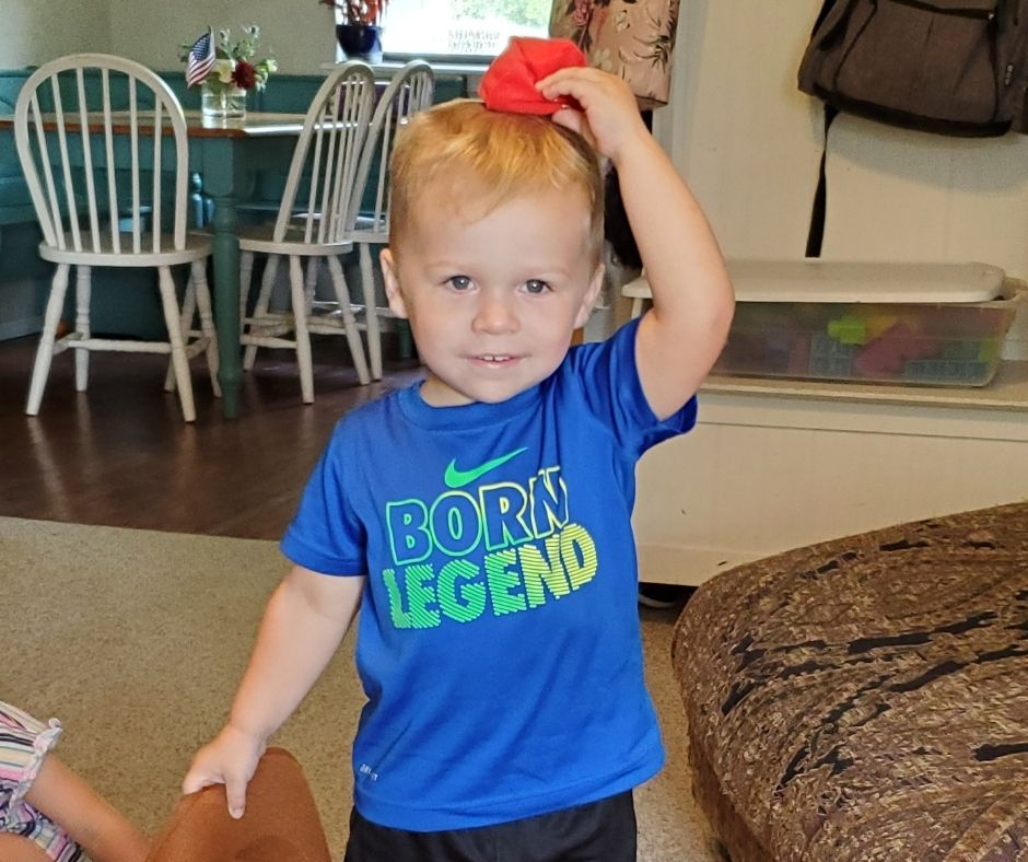 a child putting a cirlce bean bag on the top of his head