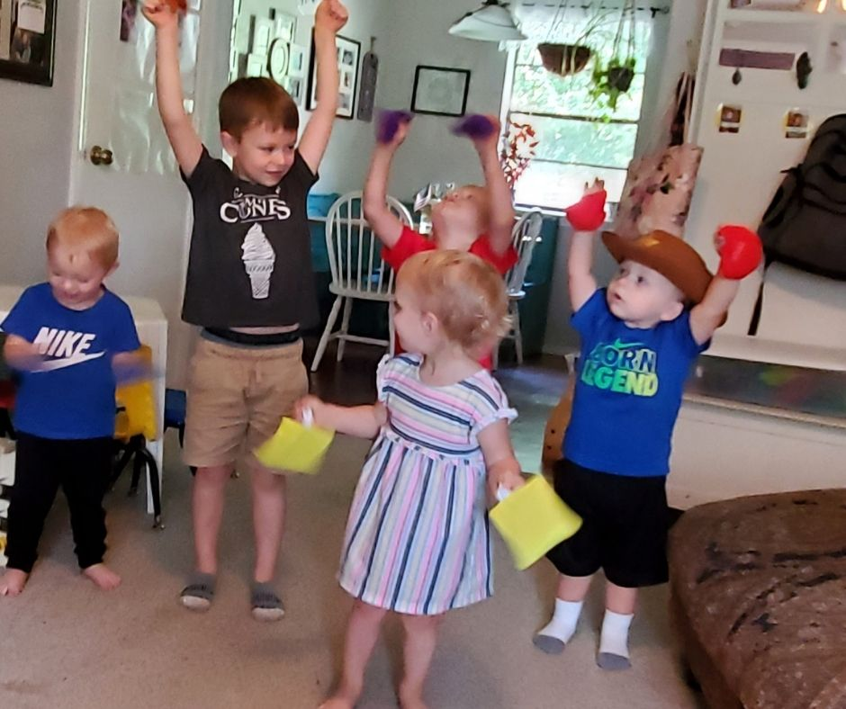 kids learning shapes with shape bean bags, playing a game where they lift their shapes into the air.