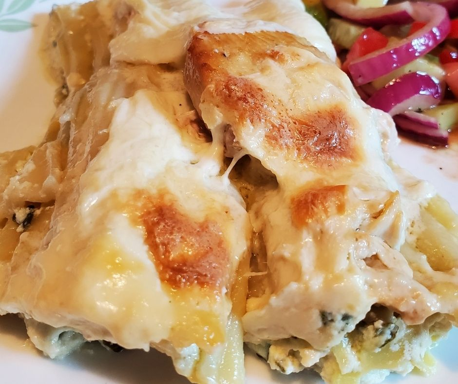 serving of chicken manicotti on a plate with a marinated salad