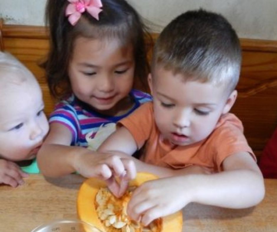 kids exploring pumpkin guts in home daycare at the table