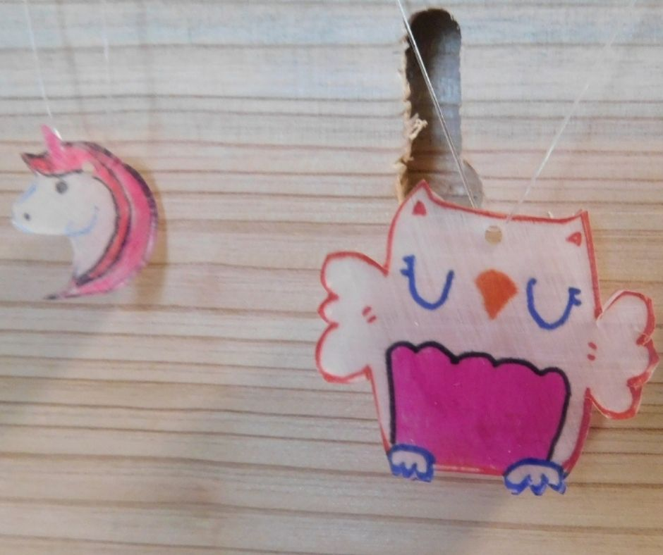 unicorn and owl shrinky dink necklaces hanging on board