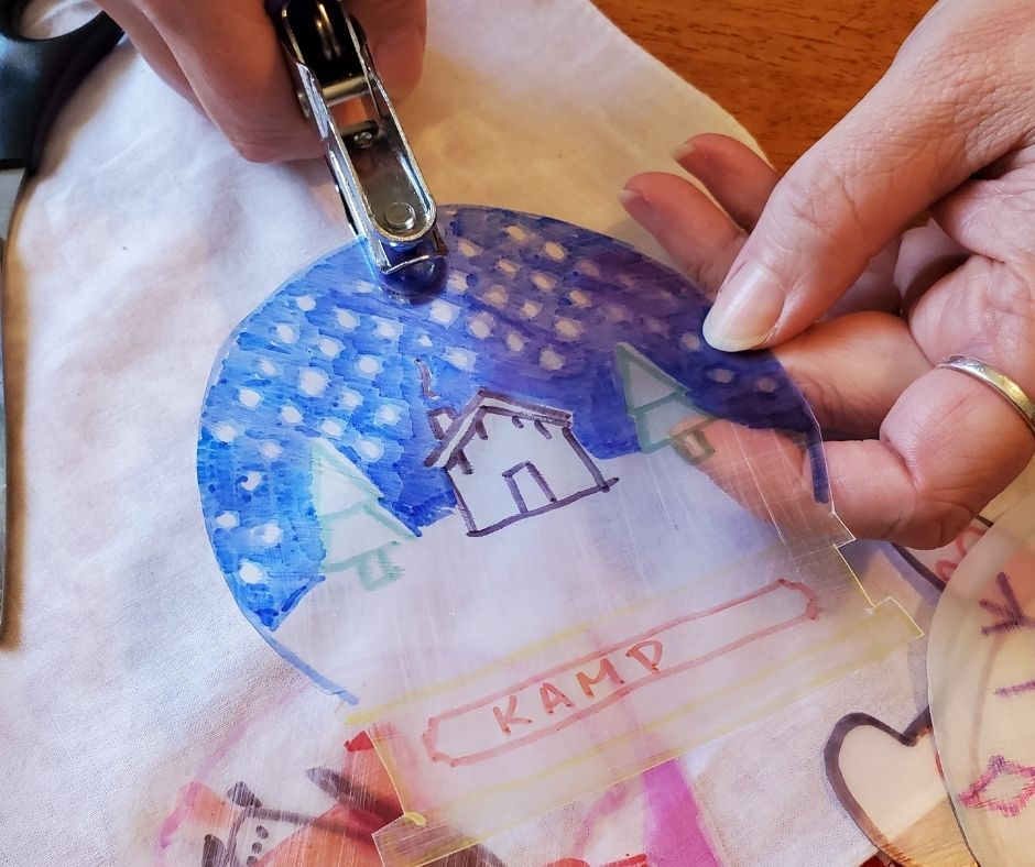 punching a hole in the top of shrinky dink before baking