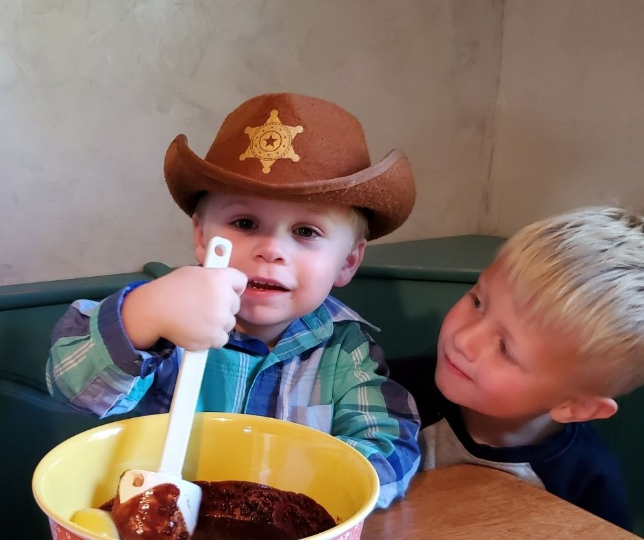 child mixing batter with a spoon at the table while another child looks at him