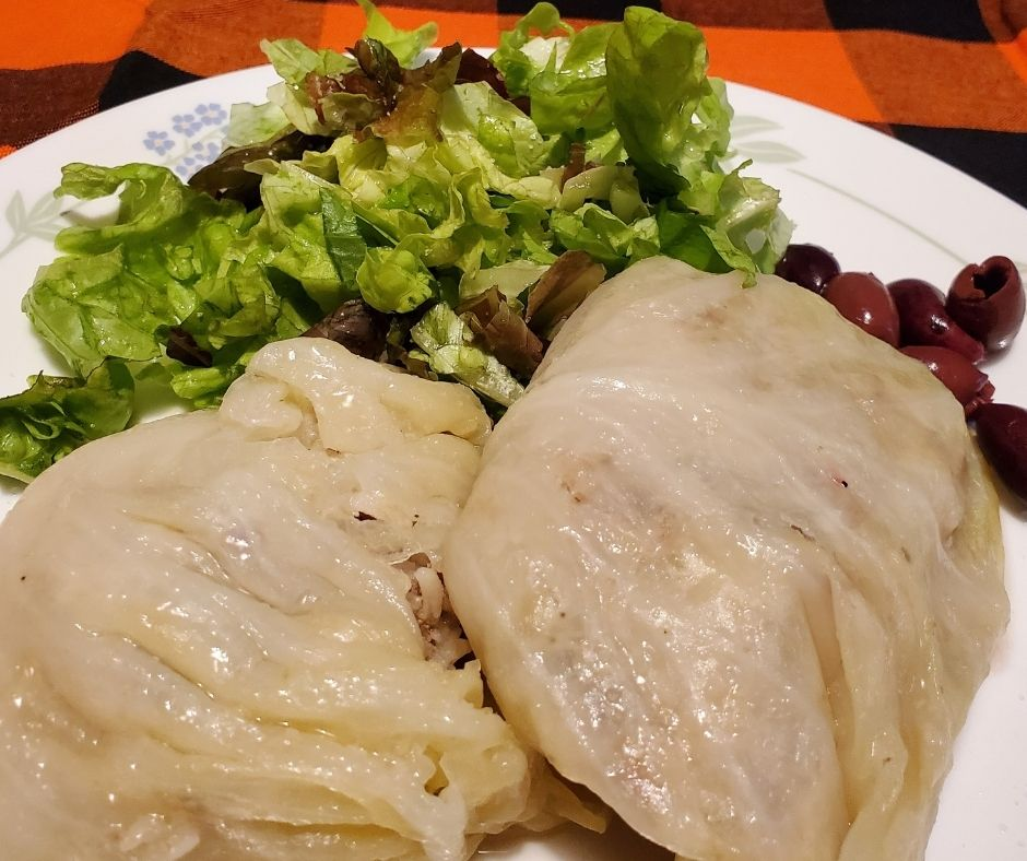 sausage cabbage rolls on a plate with salad and olives