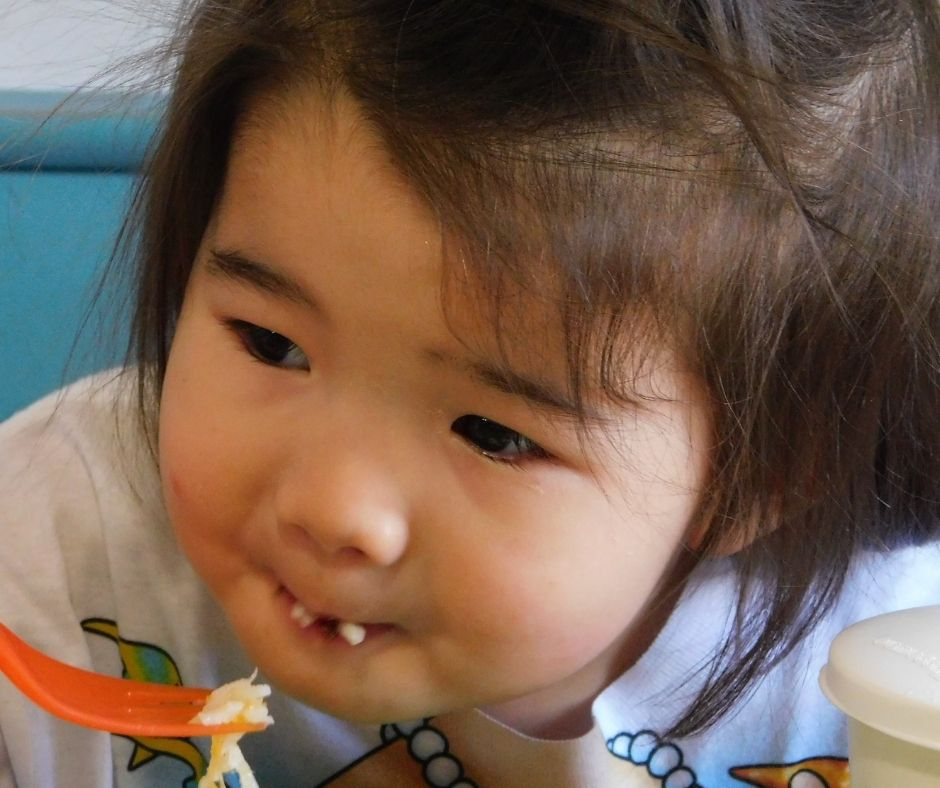 child eating snack with a fork at the table