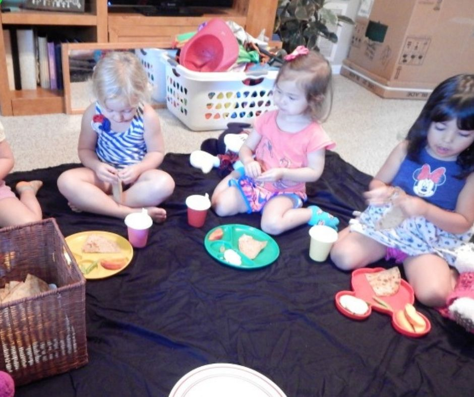 Kids eating snack on the floor at a picnic