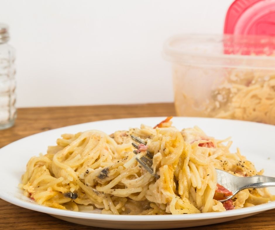 leftover chicken in pasta on a plate on a table with a container of chicken behind
