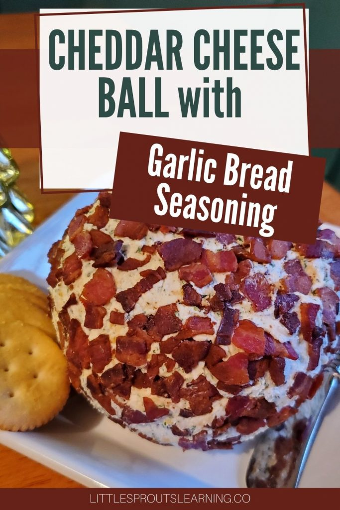 Cheddar cheese ball with garlic bread seasoning mix rolled in bacon on a plte with crackers and a spreader