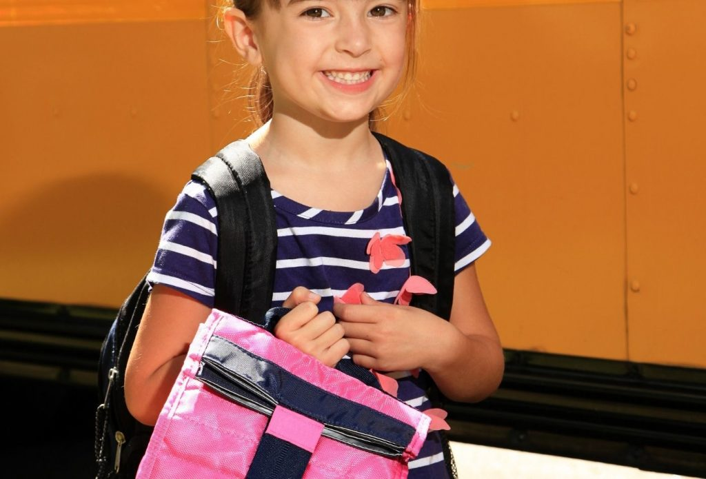 Child holding her lunch bag ready for school