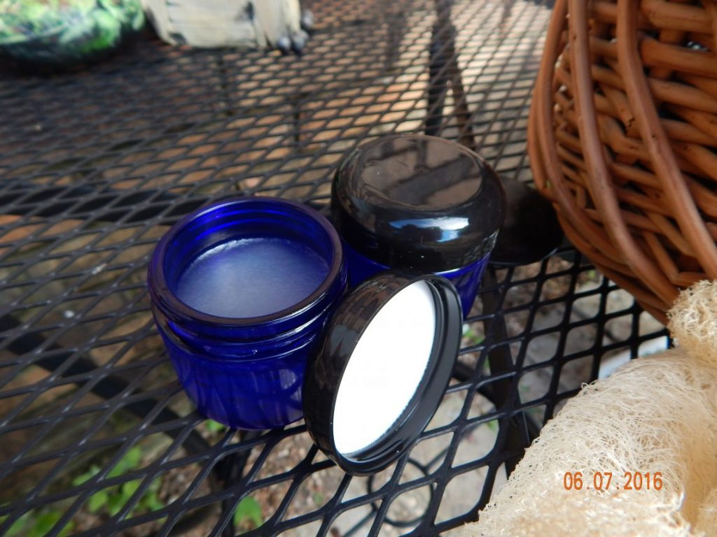 Two pots of pain relief cream on a table outside