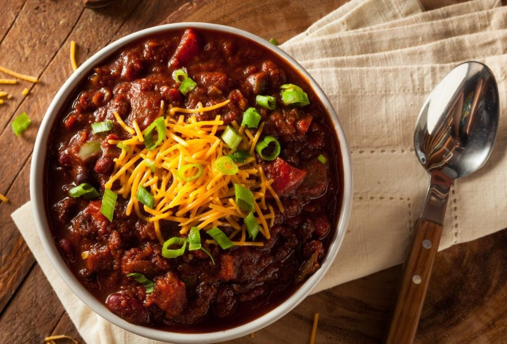 Bowl of brisket chili topped with cheese and scallions on a napkin
