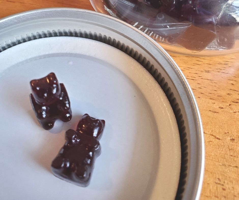 Elderberry gummies on the lid of a mason jar next to the jar on the table