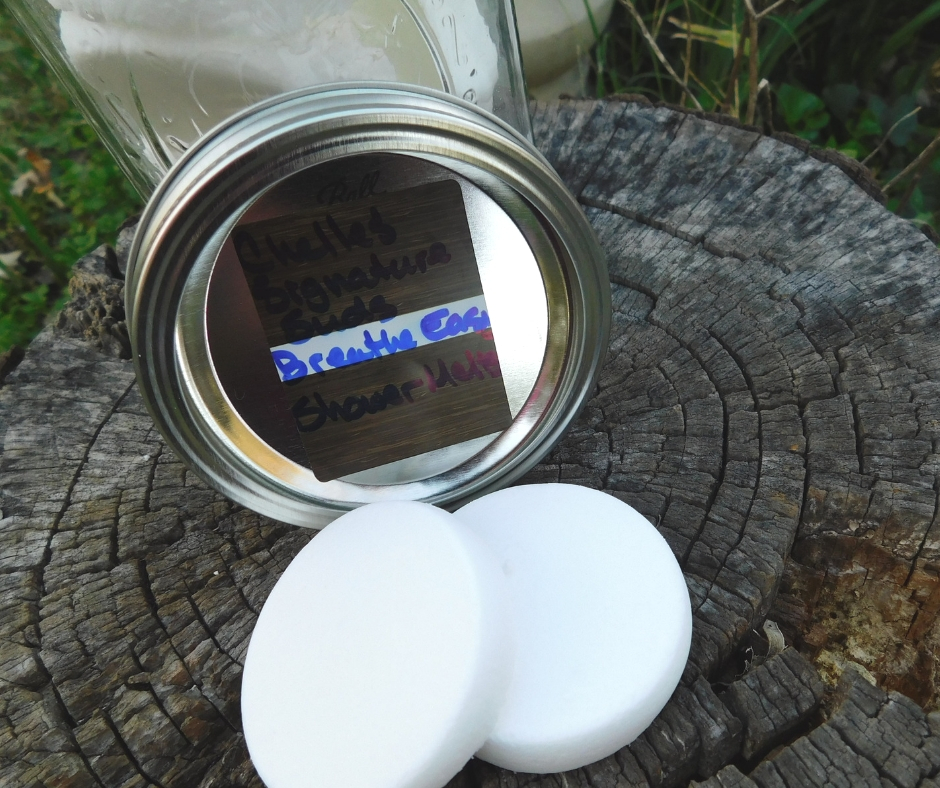 Shower vapor tablets and a jar sitting on the top of a stump