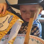 child in a cowboy hat pouring corn into a bowl to make elote in a cup