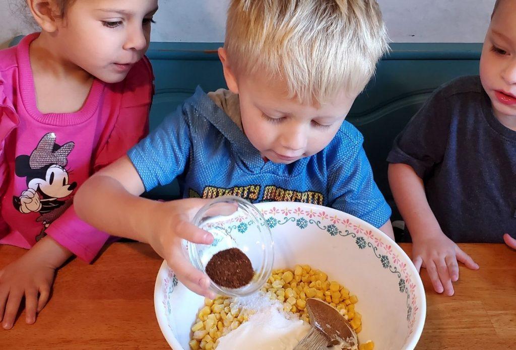 a child pouring chili powder into elote in a cup recipe