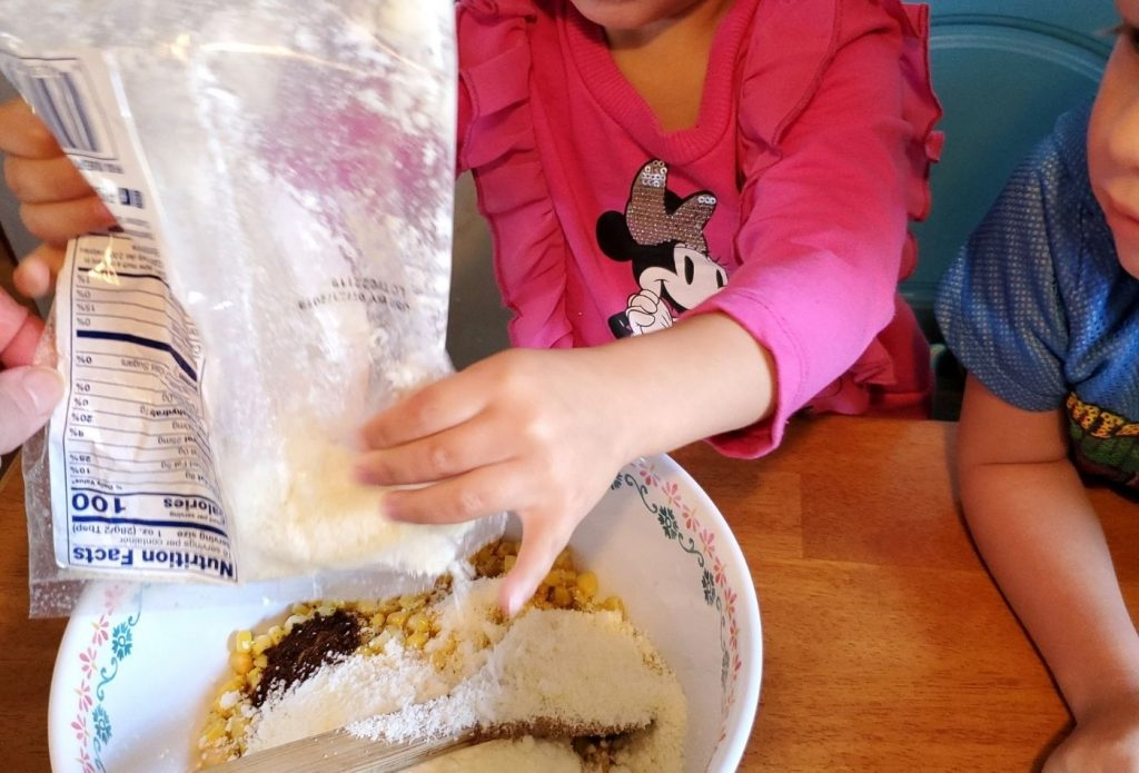 A child pouring cotija cheese into elote in a cup recipe