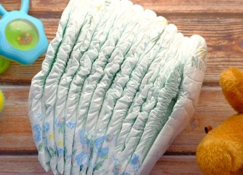 Stack of diapers, teddy bear, and rattles on a table