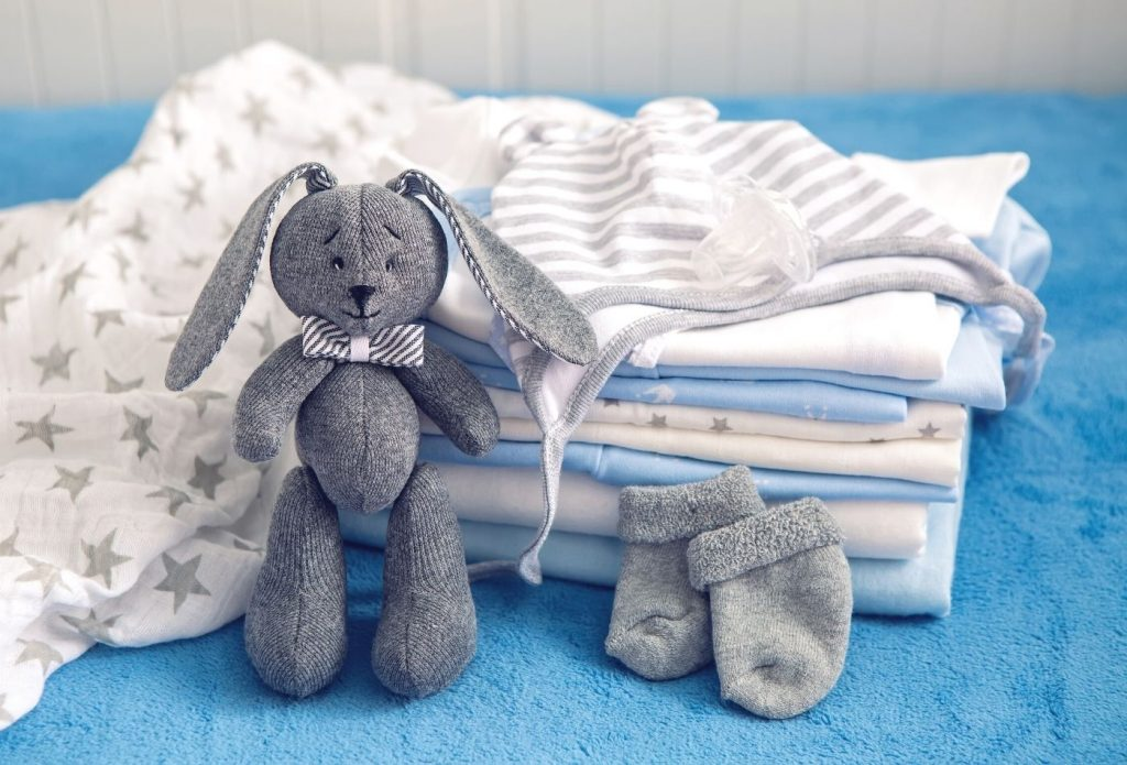 stack of baby onsies with socks and a stuffed bunny