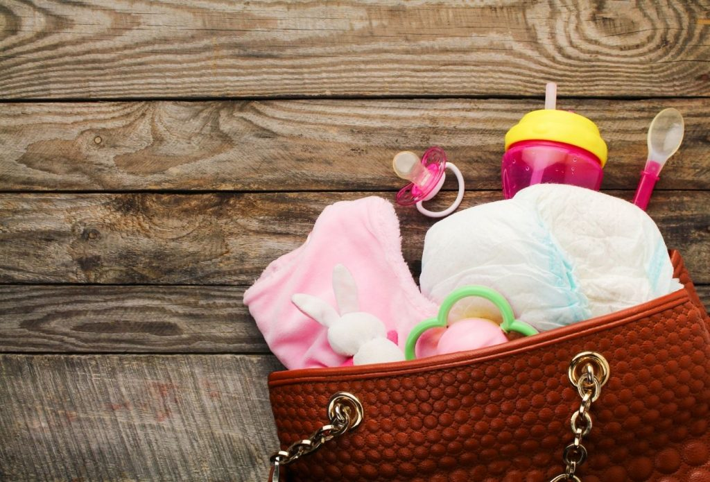 Diaper bag with cup, spoon, pacifier, change of clothes, diapers, and toys.