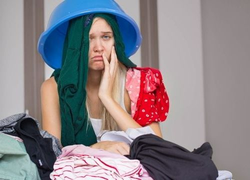 woman covered in laundry overwhelmed