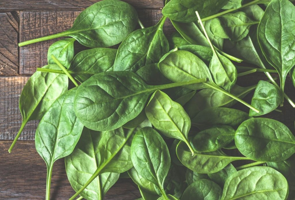 pile of fresh cut spinach on a board