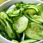 Sliced cucumbers in a bowl with onions