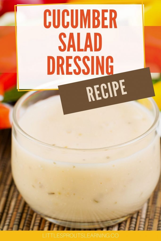 Cucumber salad dressing in a bowl in front of some sliced vegetables on a plate