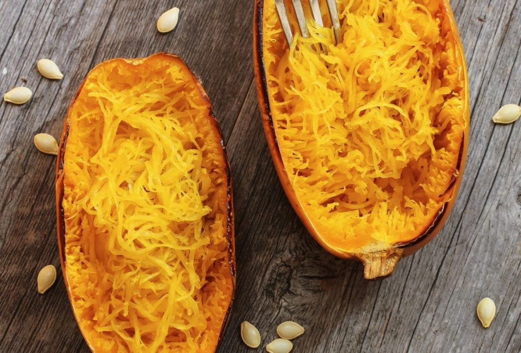 cooked spaghetti squash halves with the meat scraped out and fluffed up