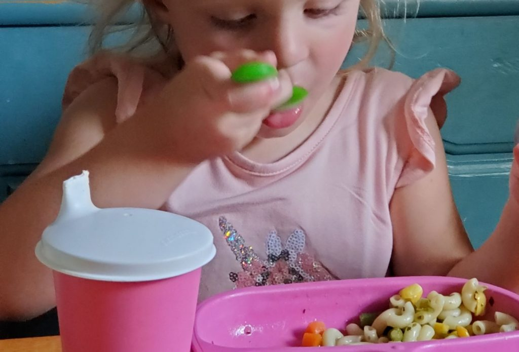 child eating vegetable soup with a pink plate, green spoon and pink cup