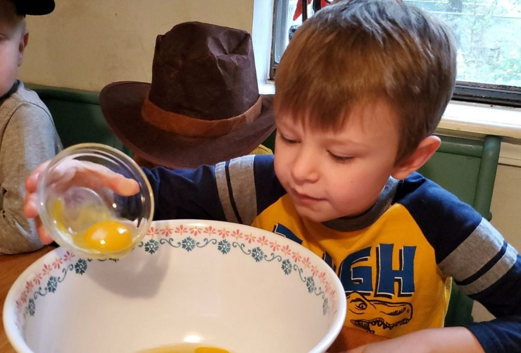 child pouring eggs into a mixing bowl for traditional pilgrim pumpkin pie