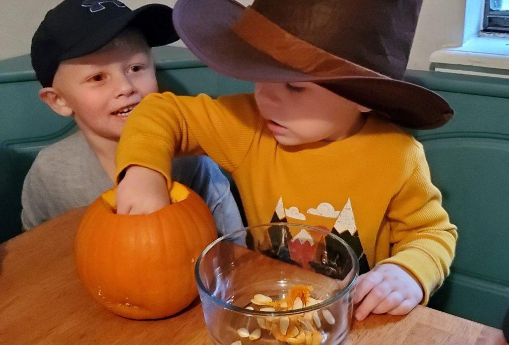 child digging pumpkin guts from a pumkin shell