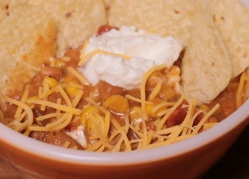 taco soup in a bowl with cheese, sour cream, and chips on top