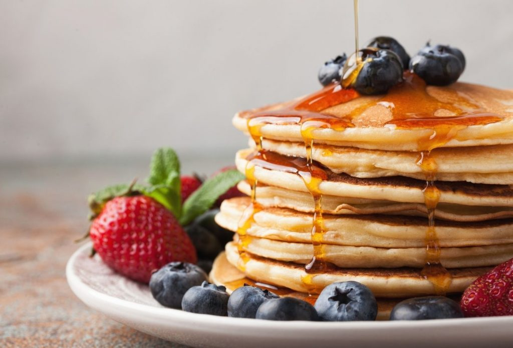 stack of pancakes with fruit and syrup for meatless monday breakfast